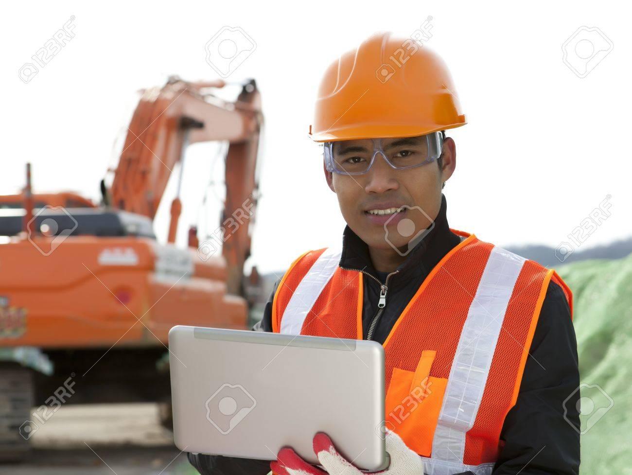 road construction worker using laptop standing front excavator Stock Photo - 18062195