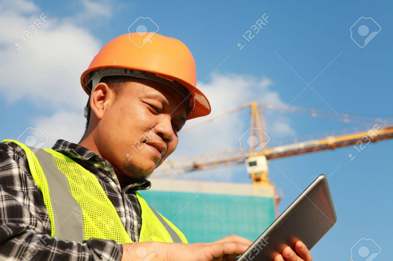 construction worker using digital tablet with crane on the background - 21963022