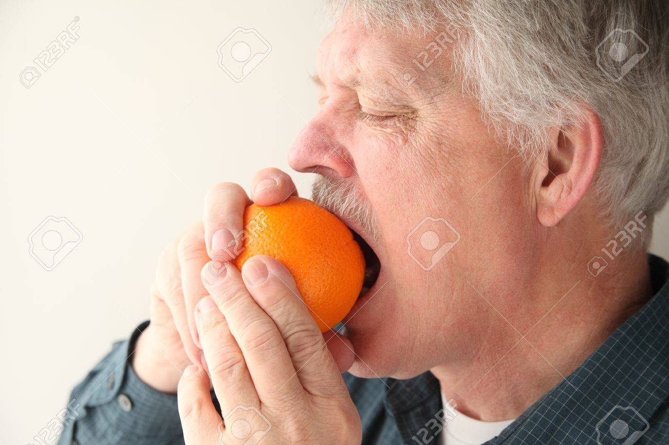 Older Man Bites Into Orange To Start The Peeling Process Stock ...
