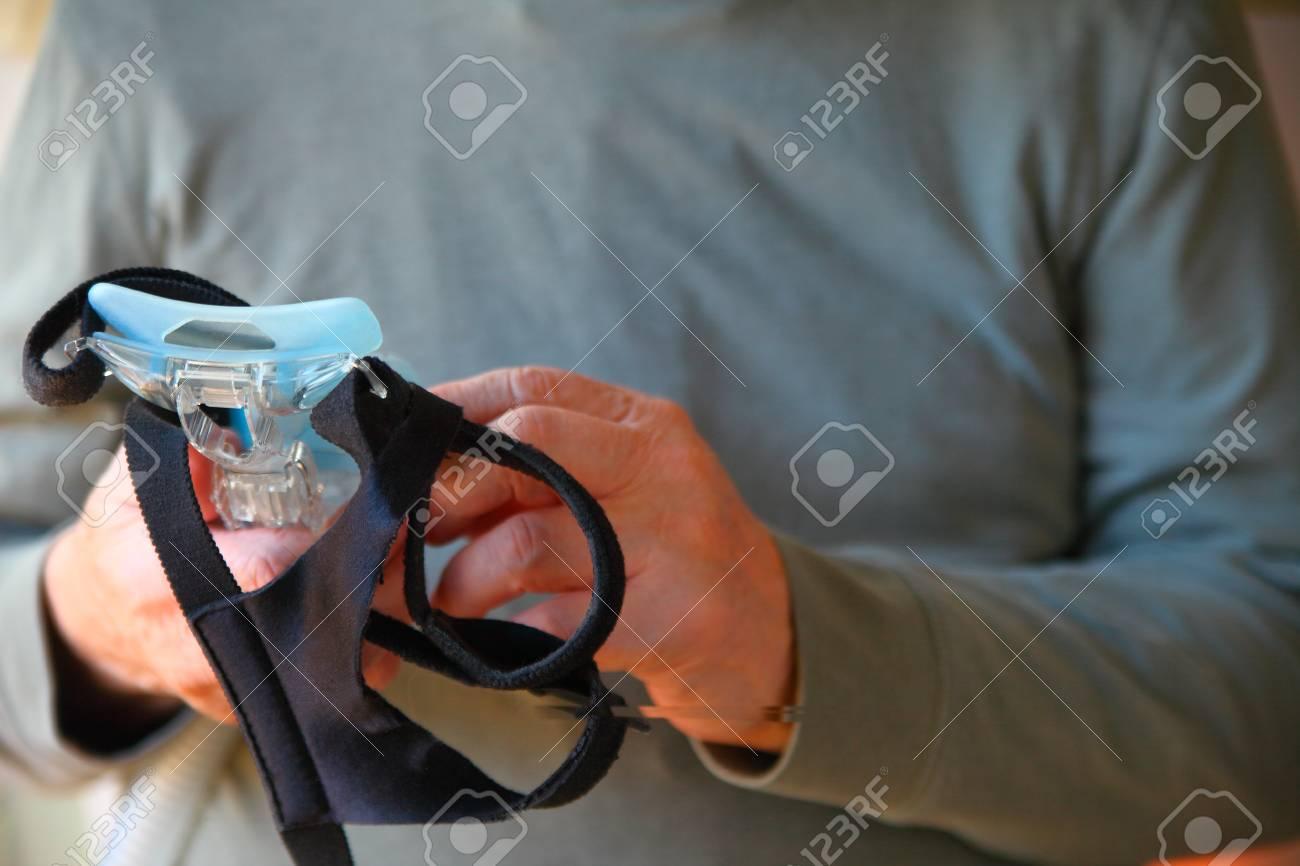 A man holds his sleep apnea face mask and headgear - 118384903