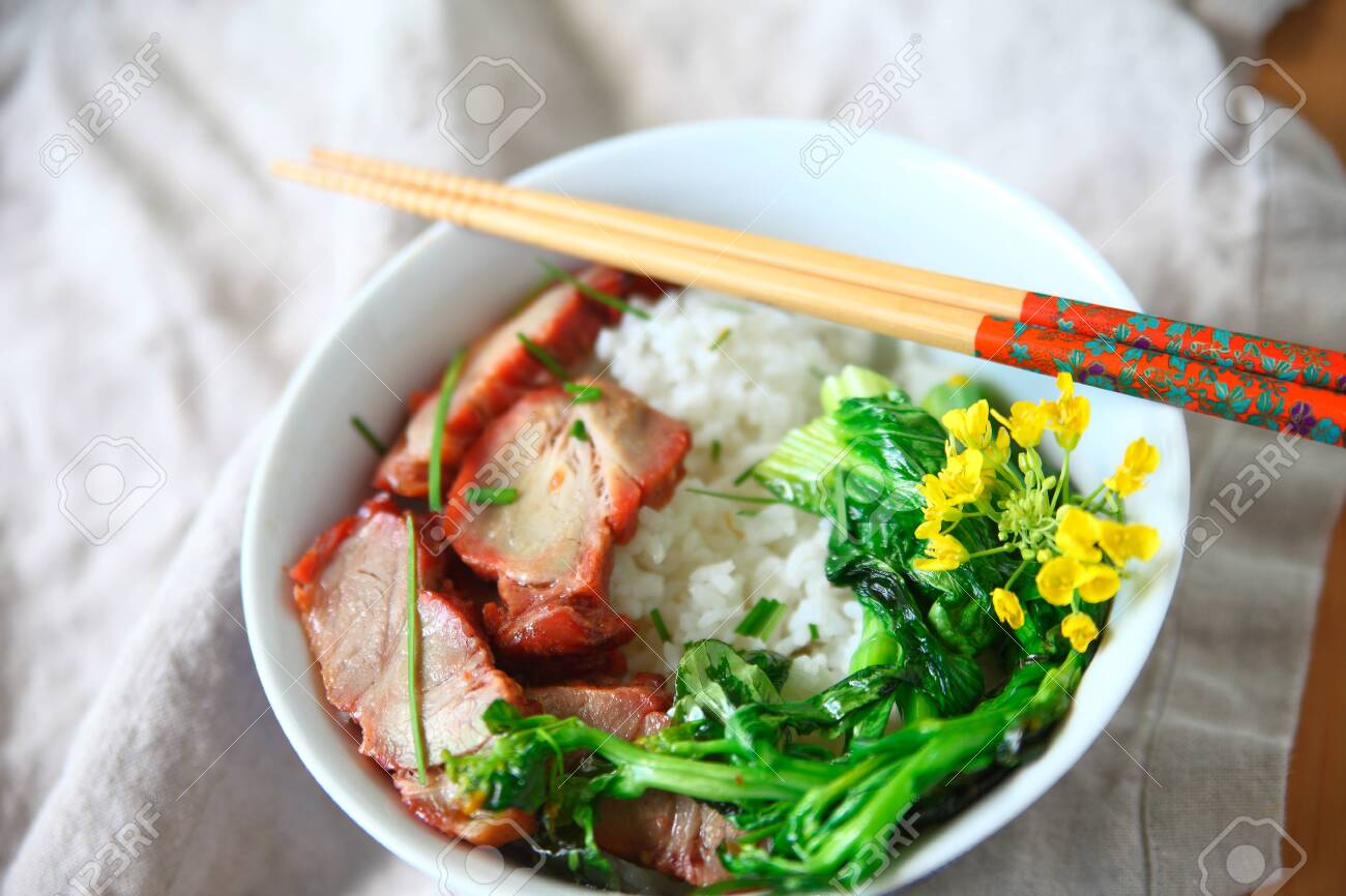 Roast pork and Asian greens with edible flowers on rice - 141339022