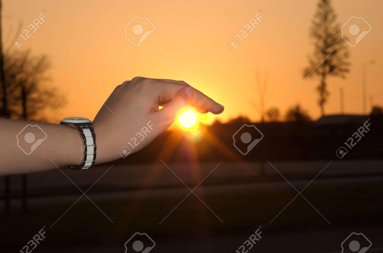 Girls hand pushing the sun down in the sunset. Stock Photo - 4528559