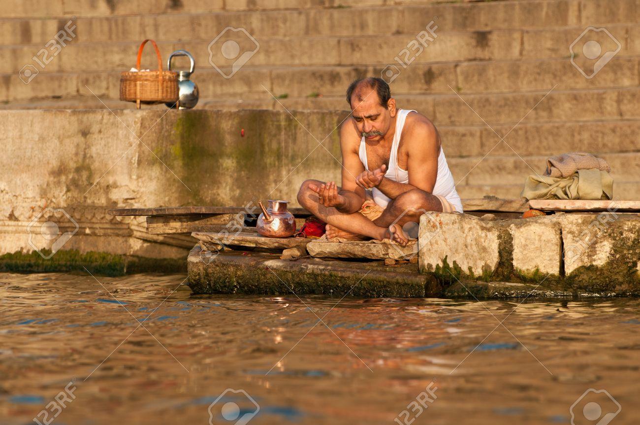 VARANASI, INDIA - FEBRUARY 19, 2012: A Hindu brahmin priest offers prayers on the bank of holy Ganges river on the auspicious Maha Shivaratri festival on February 19, 2011 at Varanasi, Uttar Pradesh, India Stock Photo - 13626986