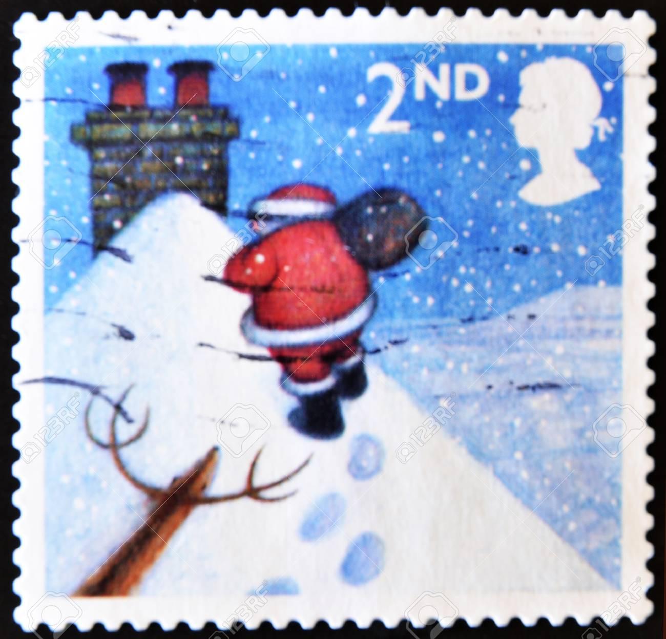 UNITED KINGDOM - CIRCA 2004: A stamp printed in England, shows Santa Claus, walking toward chimney in snow, circa 2004 Stock Photo - 11099013