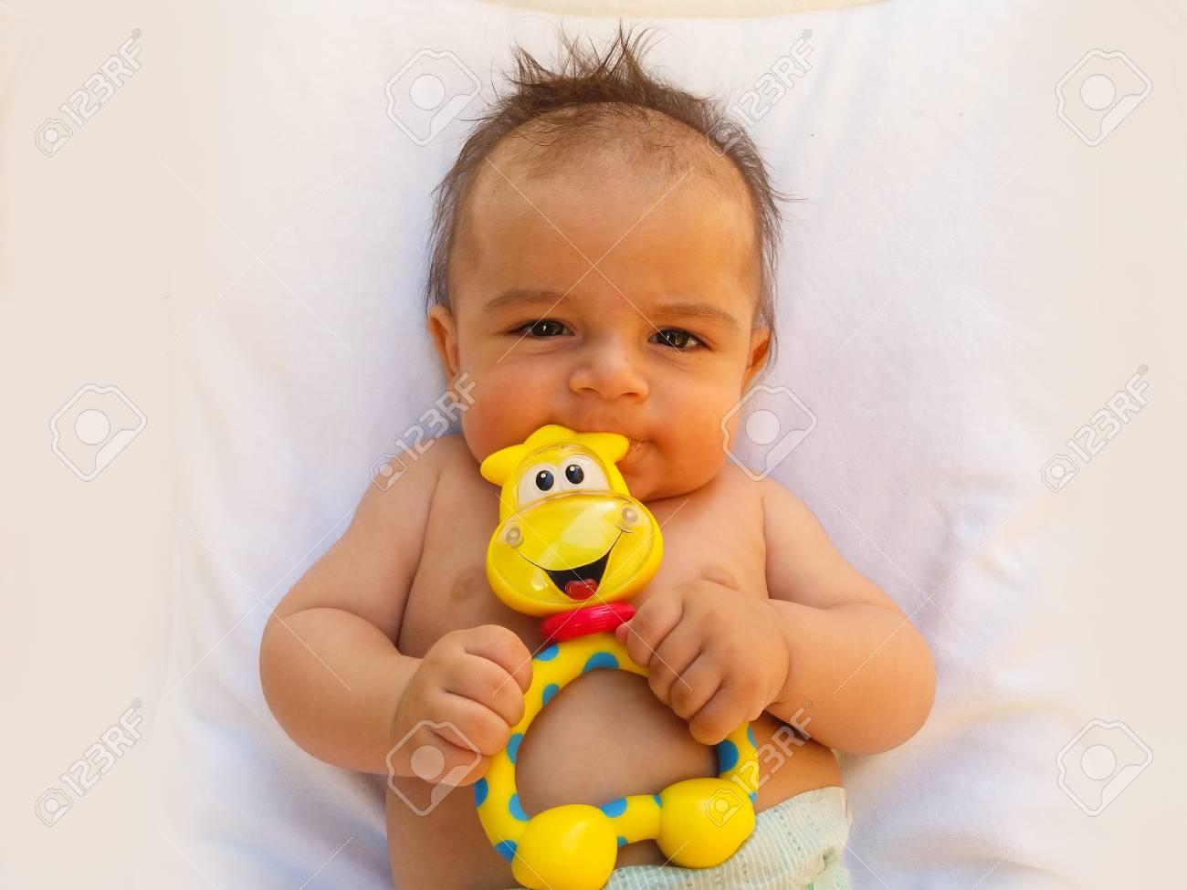 fcc0564a5b58 Bebé de 3 meses que juega con el juguete de la dentición Foto de archivo -