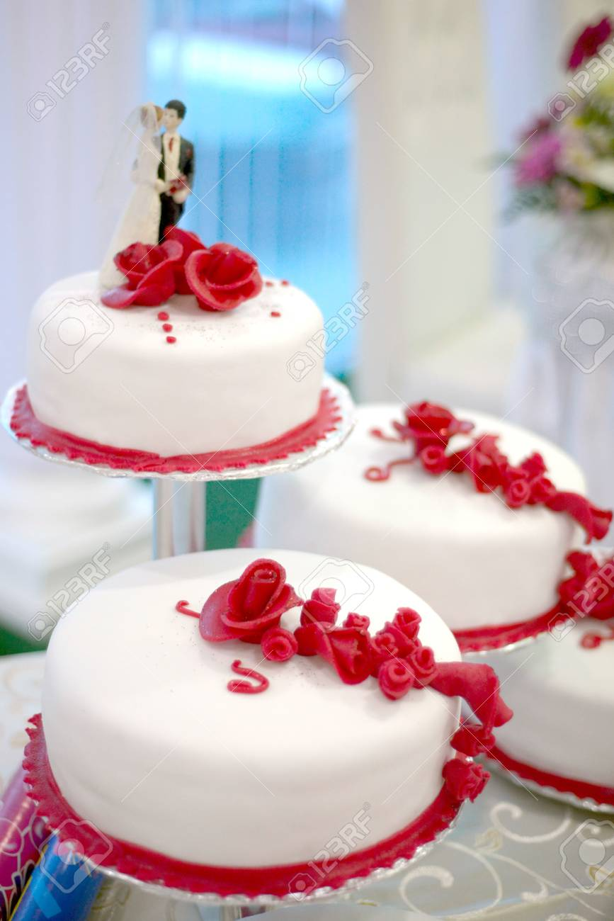 White Wedding Cake With Red Roses And Figurines Of Bride And Stock