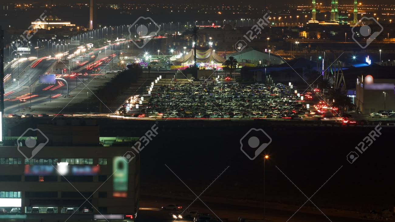 Cityscape of Ajman with traffic on car parking mear mall from