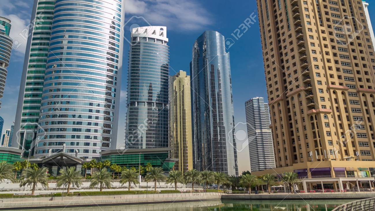Timelapse view on skyscrapers at waterfront. Residential buildings in Jumeirah Lake Towers reflected in water in Dubai, UAE. The JLT is a large development which consists of 79 towers with 3 artificial lakes and park. View with blue cloudy sky from embankment - 109140207