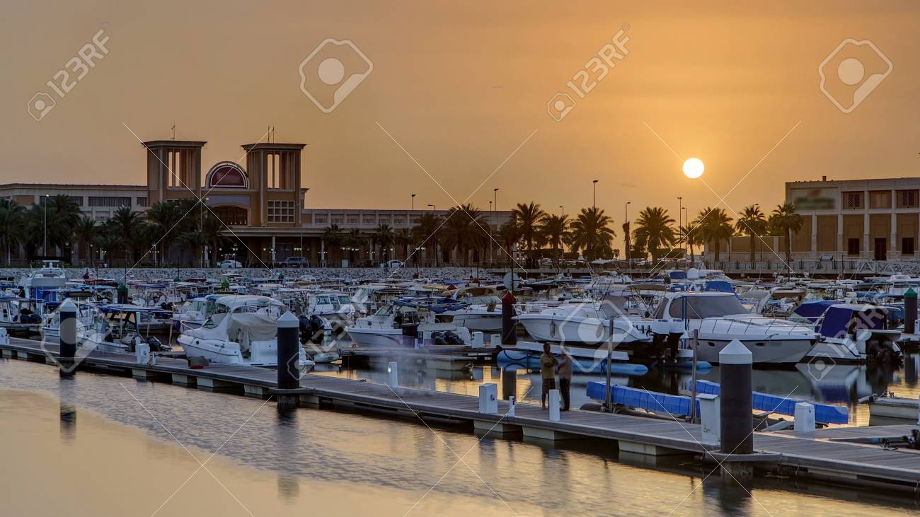 Yachts and boats at the Sharq Marina with fish market at sunset