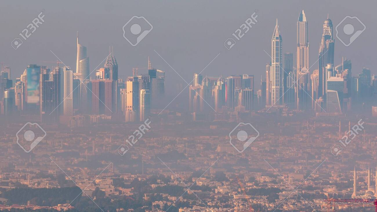 Dubai Marina and Jumeirah beach during sunrise with early morning fog timelapse in Dubai, United Arab Emirates. Aerial view from downtown with skyscrapers, villas and mosque - 128944239