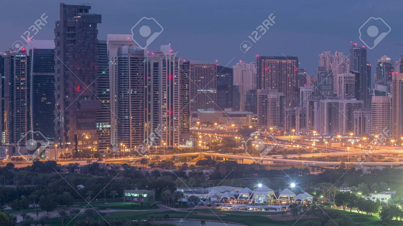 Jumeirah lake towers and Dubai marina skyscrapers and golf course night to day transition timelapse, Dubai, United Arab Emirates. Aerial view from Greens district before sunrise - 128945877