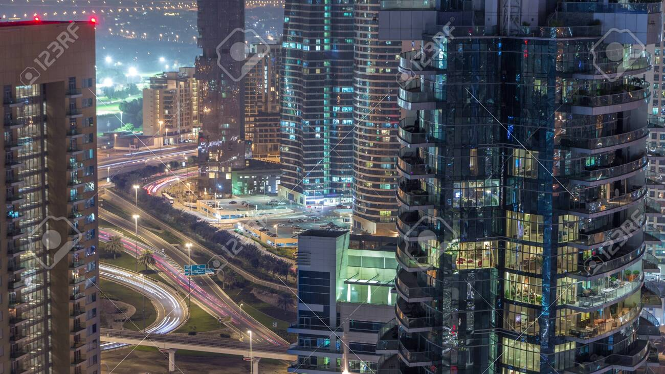 Aerial view of a road intersection in a big city night timelapse. Urban landscape of Dubai Marina and JLT district in UAE with cars and metro - 128955404