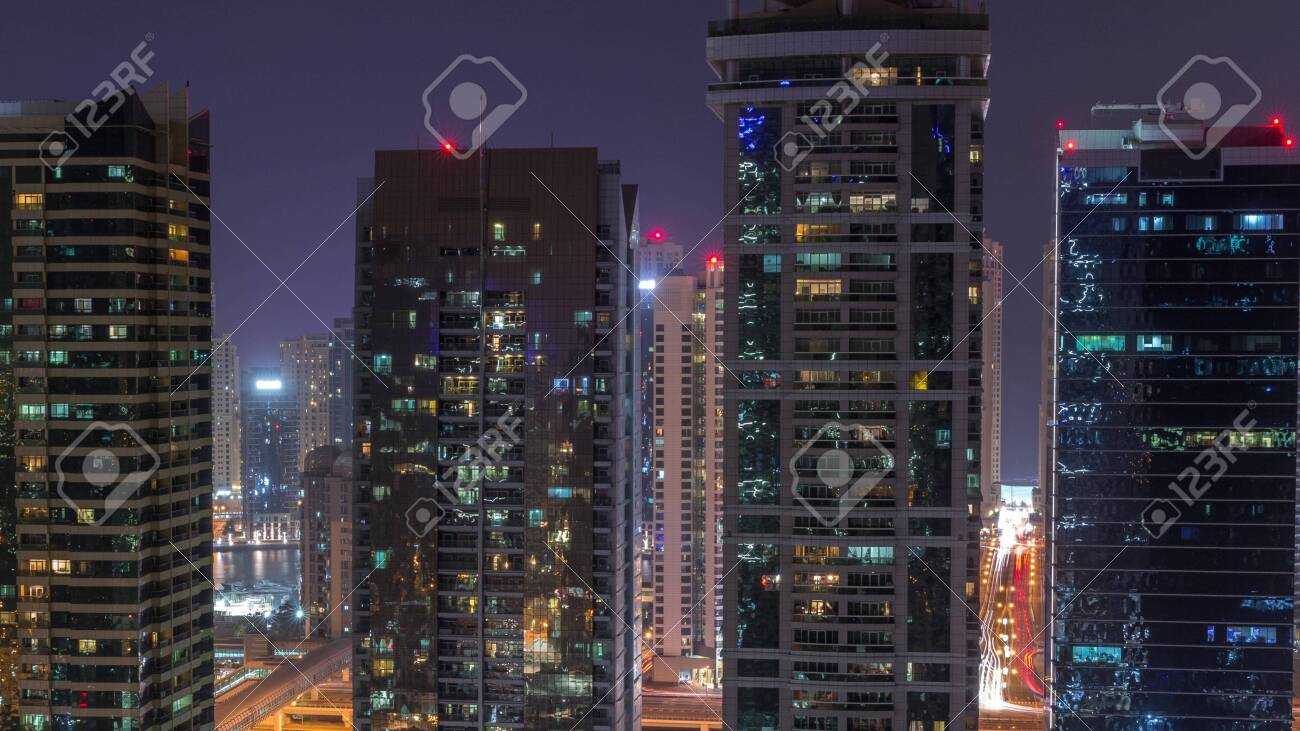 Residential and office buildings in Jumeirah lake towers district night timelapse in Dubai. Aerial panoramic view from above with modern skyscrapers - 131321345
