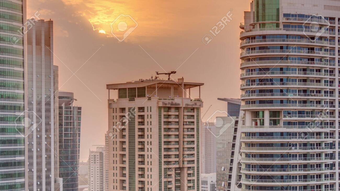 Sunset over residential and office buildings in Jumeirah lake towers district timelapse in Dubai. Aerial panoramic view from above with modern skyscrapers - 131321442