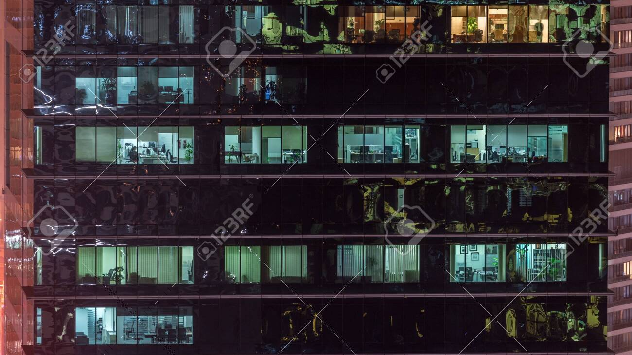 Office skyscraper exterior during late evening with interior lights on and people working inside night timelapse. Aerial close up view from above with many windows. Pan up - 131321165
