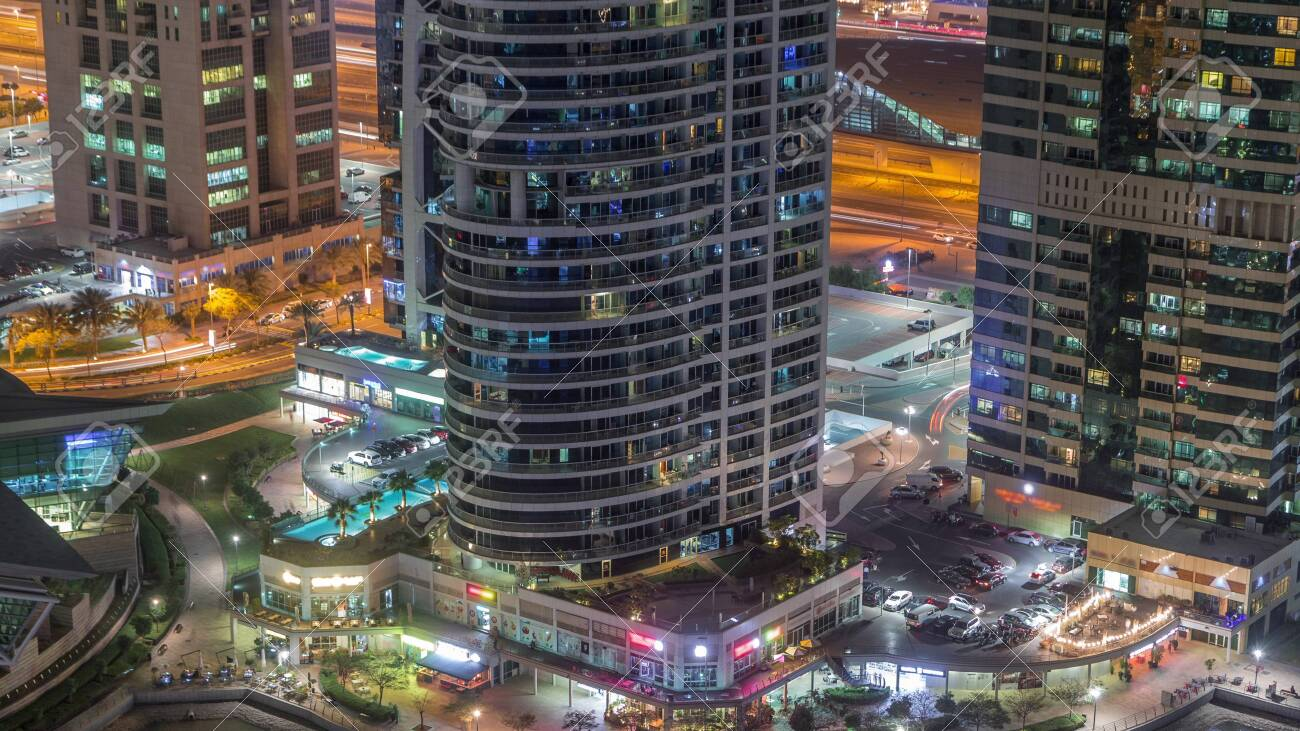 Residential and office buildings in Jumeirah lake towers district night timelapse with shops, restaurants and walkways in Dubai. Aerial panoramic view from above with modern skyscrapers - 131321386