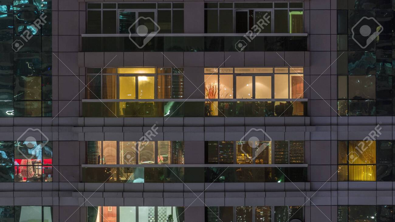 Night view of exterior apartment building timelapse. High rise skyscraper with blinking lights in windows with people moving inside. Zoom out - 131681087