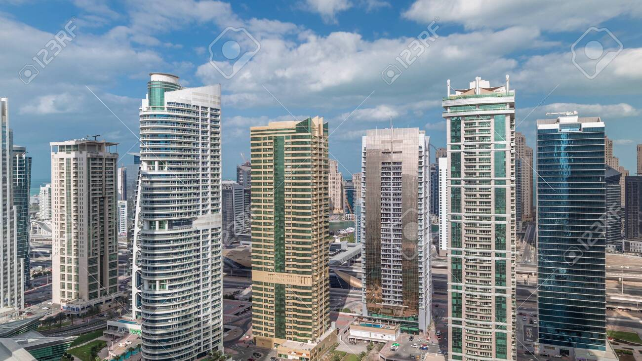 Residential apartments and offices in Jumeirah lake towers district timelapse in Dubai. Aerial panoramic view from above with modern skyscrapers and clouds on blue sky - 131321610