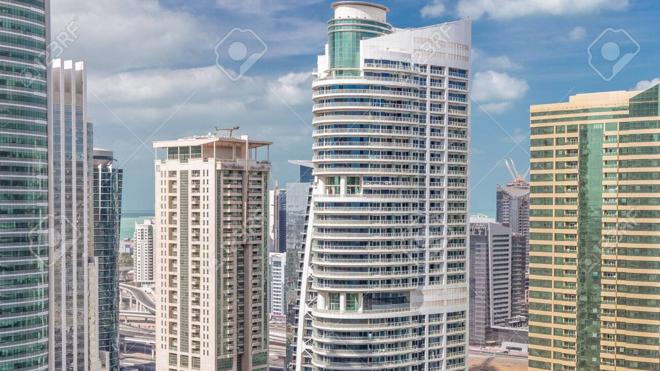 Residential apartments and offices in Jumeirah lake towers district timelapse in Dubai. Aerial view from above with modern skyscrapers and clouds on blue sky - 131321643
