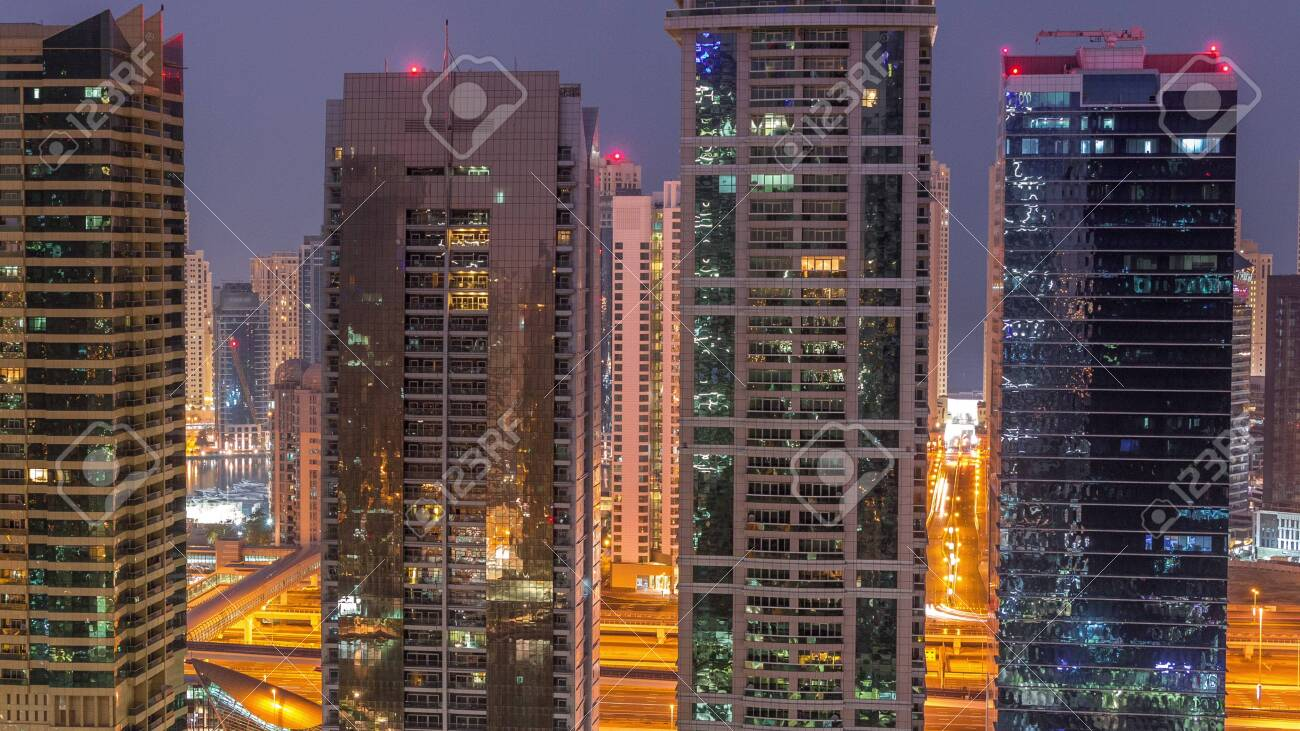 Residential and office buildings in Jumeirah lake towers district night to day transition timelapse before sunrise in Dubai. Aerial panoramic view from above with illuminated modern skyscrapers - 131321290
