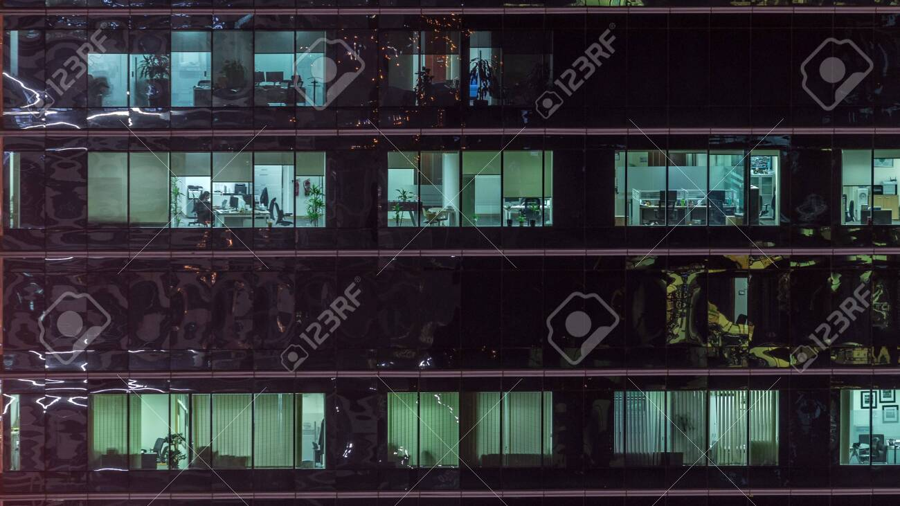 Office skyscraper exterior during late evening with interior lights on and people working inside night timelapse. Aerial close up view from above with many windows. Pan right - 131328768