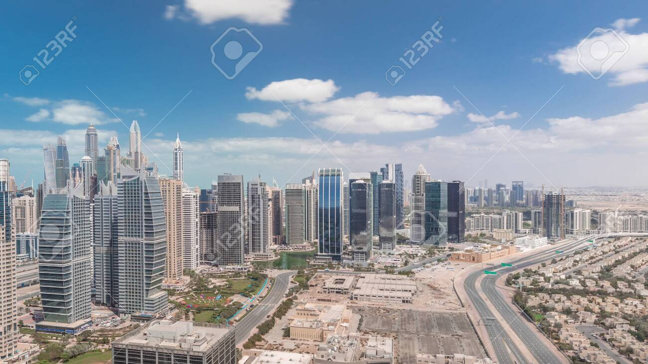 Residential apartments and offices in Jumeirah lake towers district timelapse in Dubai. Aerial panoramic view from above with modern skyscrapers and clouds on blue sky - 131328410