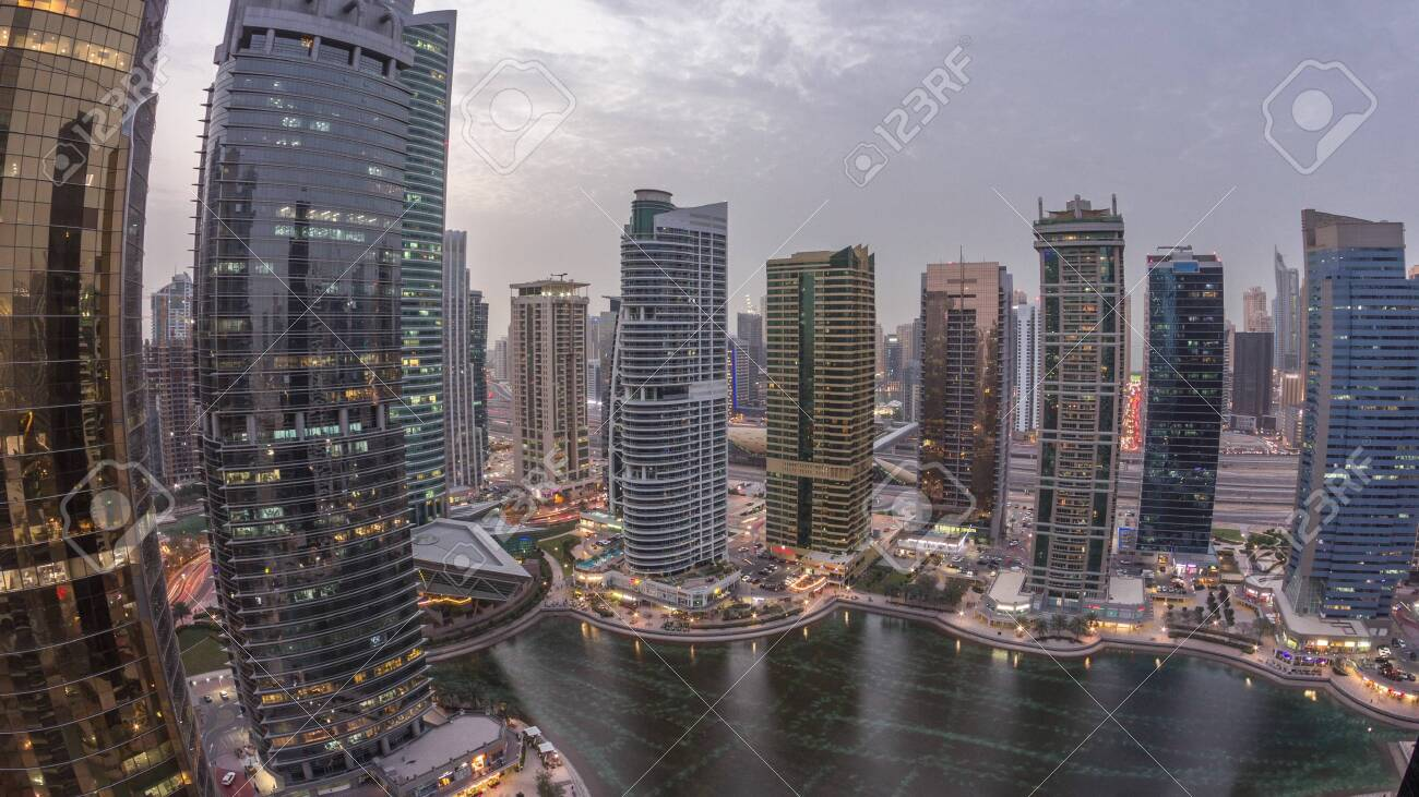 Residential and office buildings in Jumeirah lake towers district day to night transition timelapse in Dubai. Aerial panoramic view from above with modern skyscrapers - 131330943