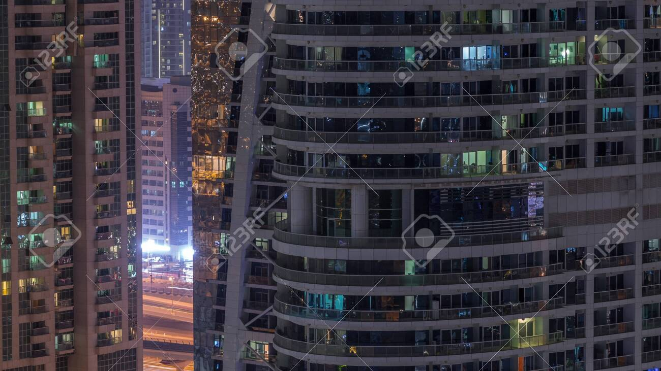Residential and office buildings in Jumeirah lake towers district night timelapse with blinking lights in windows in Dubai. Aerial view from above with modern skyscrapers - 131331111