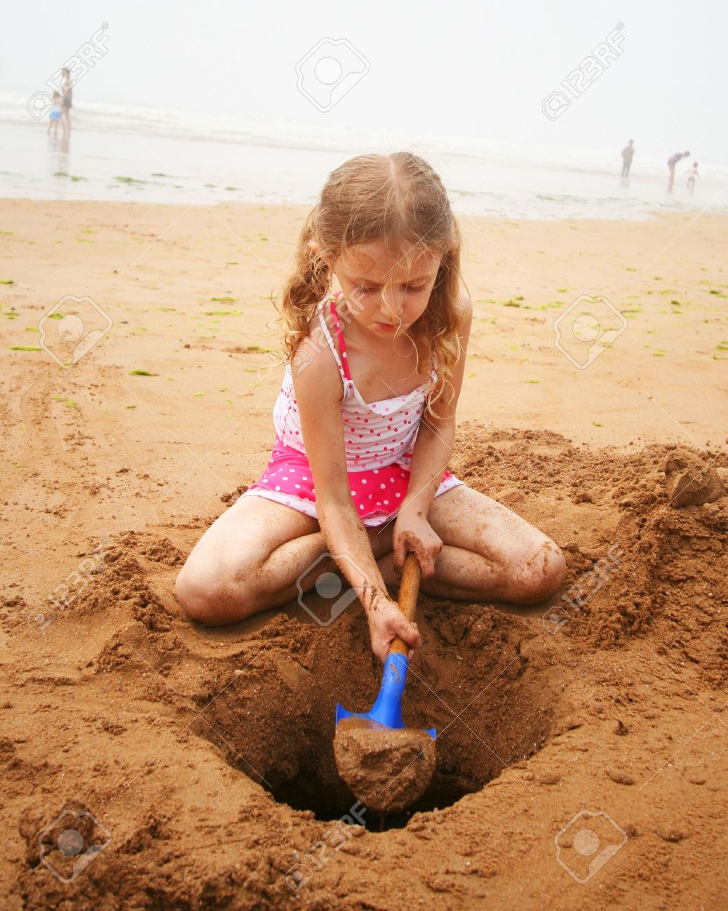 A Little Girl in a Pink Polkadot Swimsuit Digging at the Beach with a Blue Shovel Stock Photo - 7700599