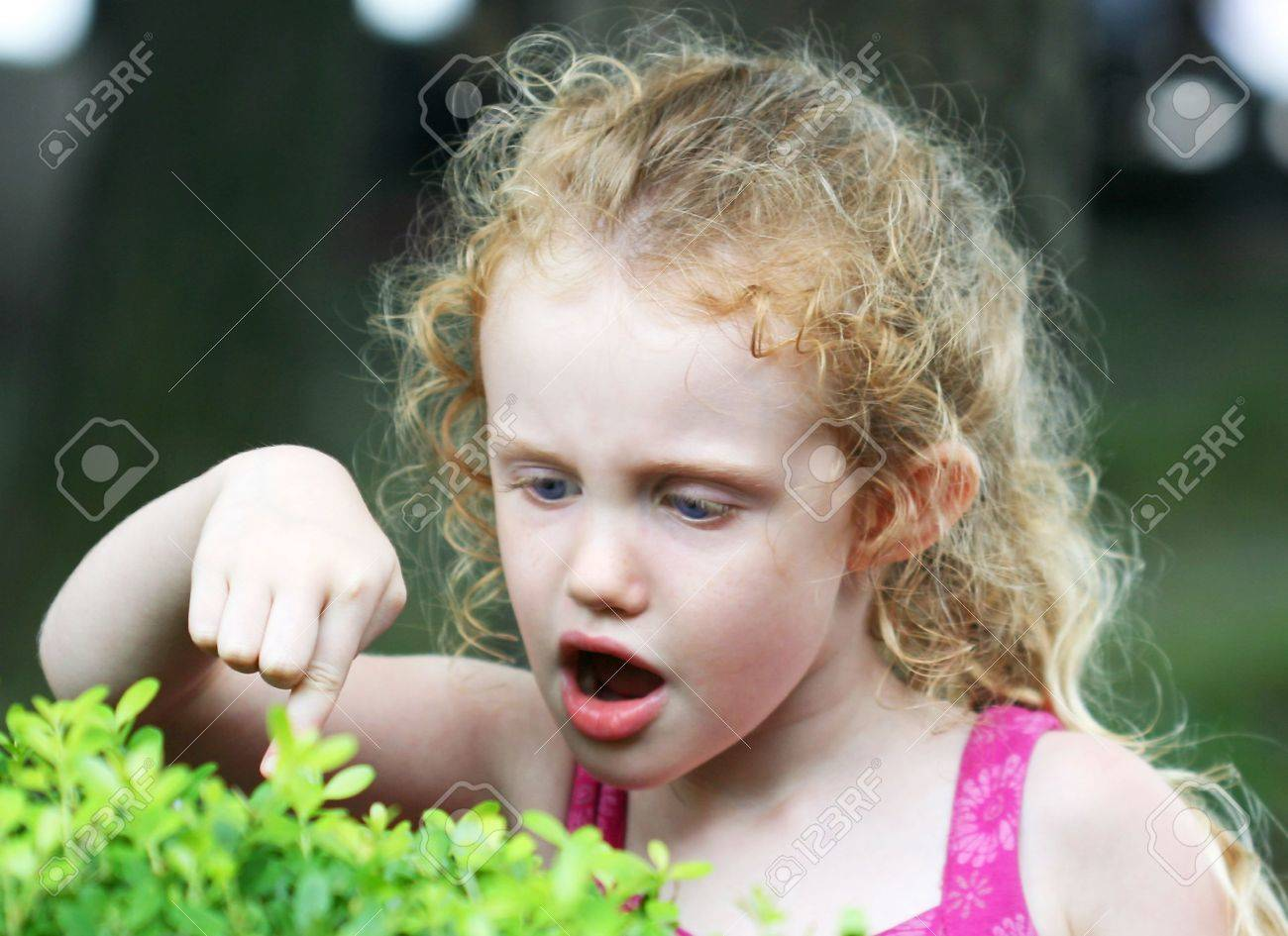 A Little Girl with Big Blue Eyes Makes a Discovery Stock Photo - 7700600