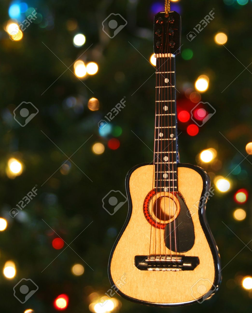 A Folk Guitar Ornament And Lights On A Christmas Tree Stock Photo ...