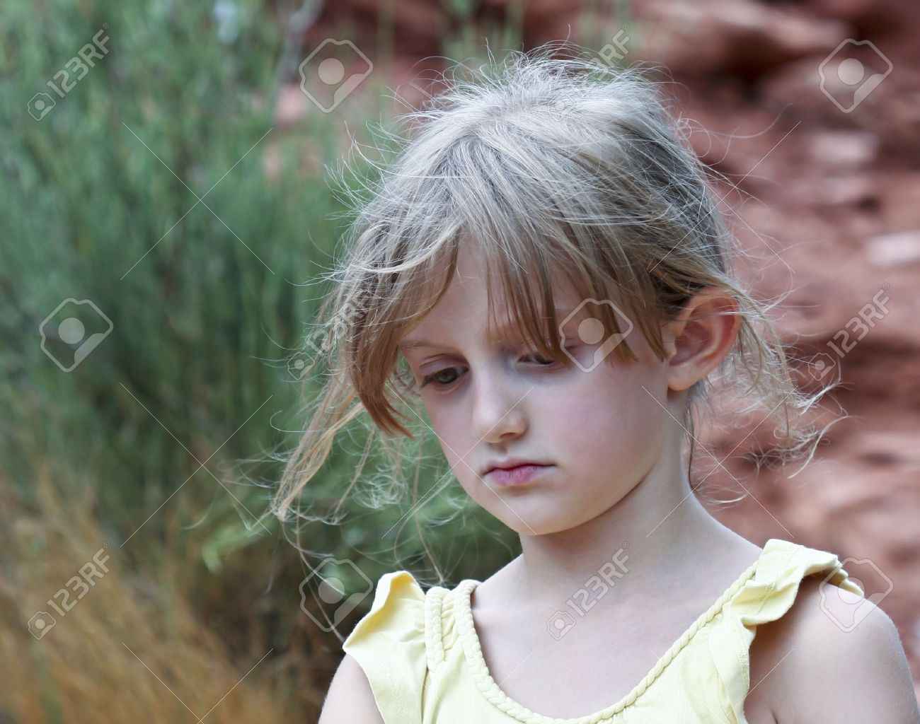 blonde little girl A Sad Little Girl with Wispy Blonde Hair in a Yellow Top Stock Photo -  10226740