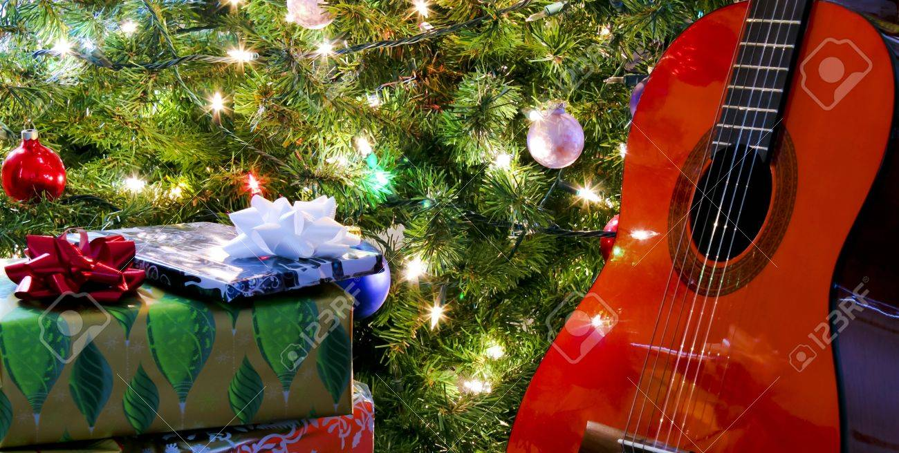A Red Classical Guitar And Presents Under The Christmas Tree Stock ...