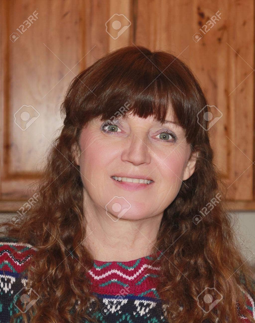 une belle femme aux cheveux auburn sourire dans un chandail coloré