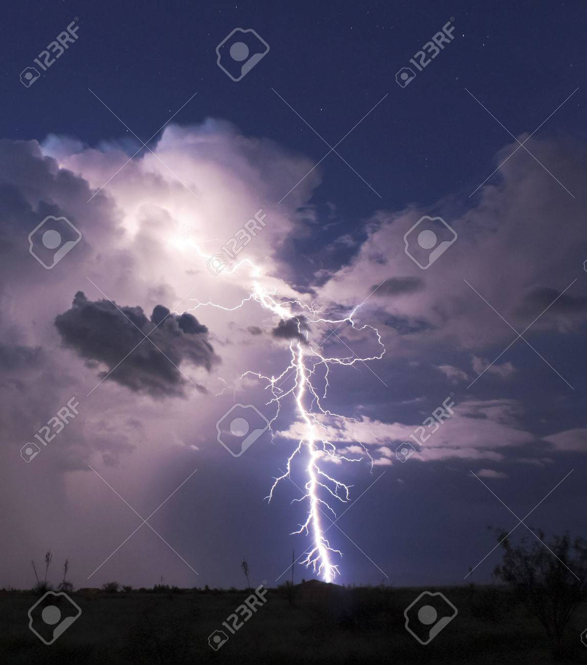 A Bolt of Lightning Strikes in a Stormy Desert Night and Seems to Hit a Housetop - 30825628