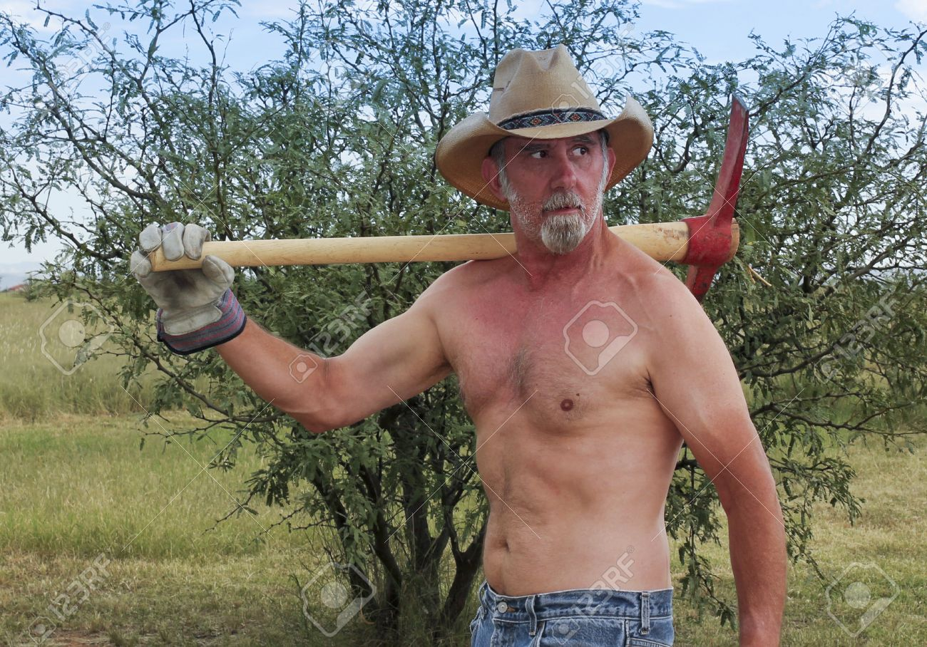 eadd10b032af3 A Shirtless Rancher in a Straw Cowboy Hat Shoulders a Red Pickax on His  Ranch Stock