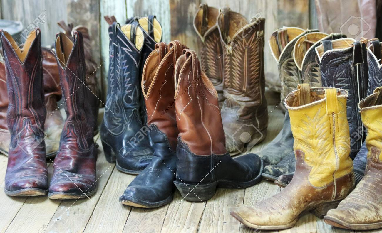A Grouping of Nine Pairs of Old Cowboy Boots on a Plank Bunkhouse Floor - 78307282
