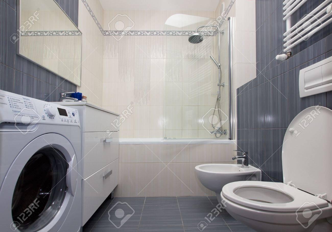 Moder lujoso cuarto de baño con azulejos grises y blancos