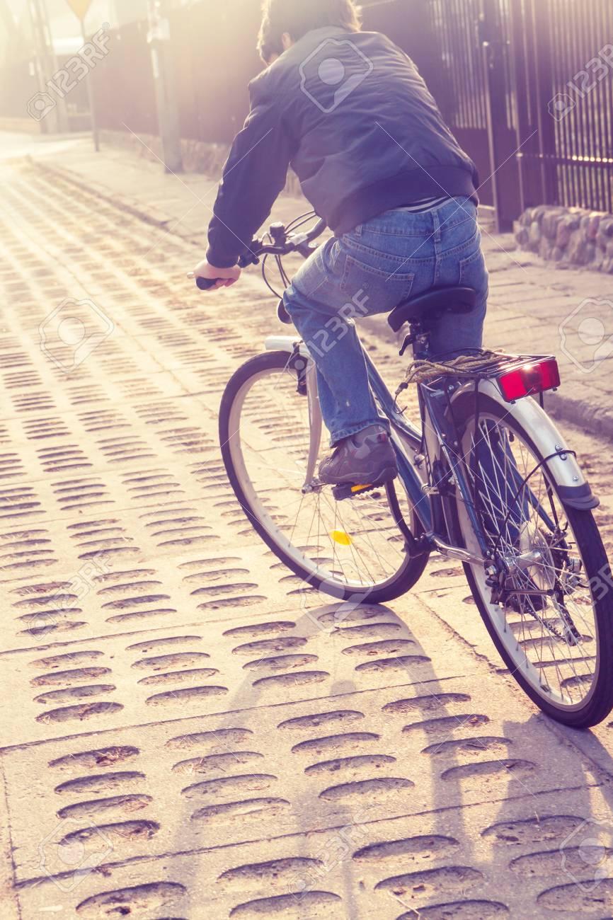 teenager boy riding bike on street, retro toned Stock Photo - 26496414