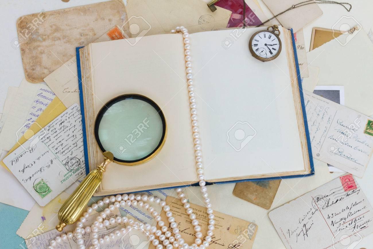81616f552a02 Foto de archivo - Viejo libro abierto vacía con lupa