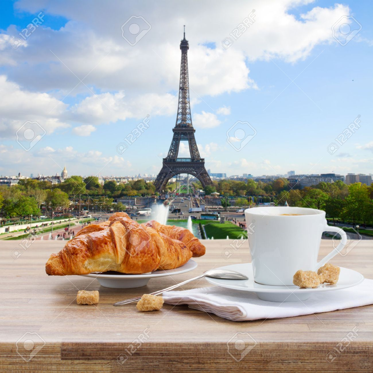 Outdoor cafe in paris with tower in background - French Cafe Cup Of Coffee With Croissant In Paris France