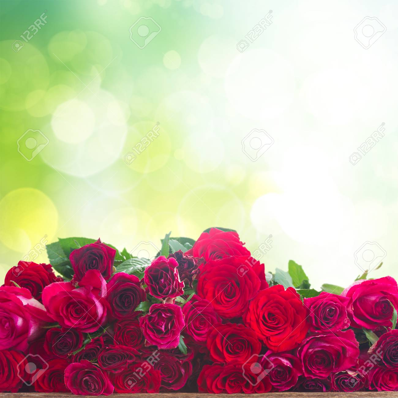 Red And Pink Roses Border On Wooden Table Over Green Garden Background Stock Photo