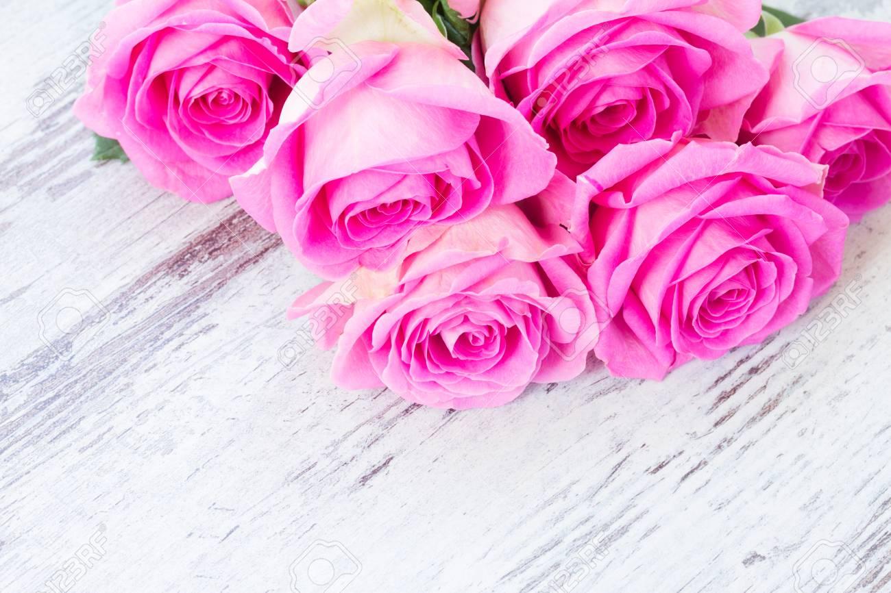 Roses roses fraîches dans l eau tombe sur le bureau vieilli en