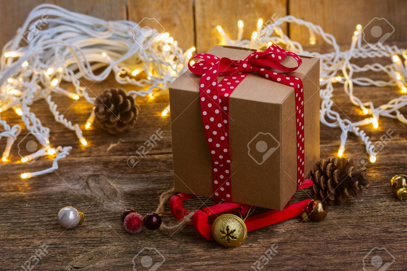 handmade gift box on sledge close up with christmas lights on wooden background stock photo