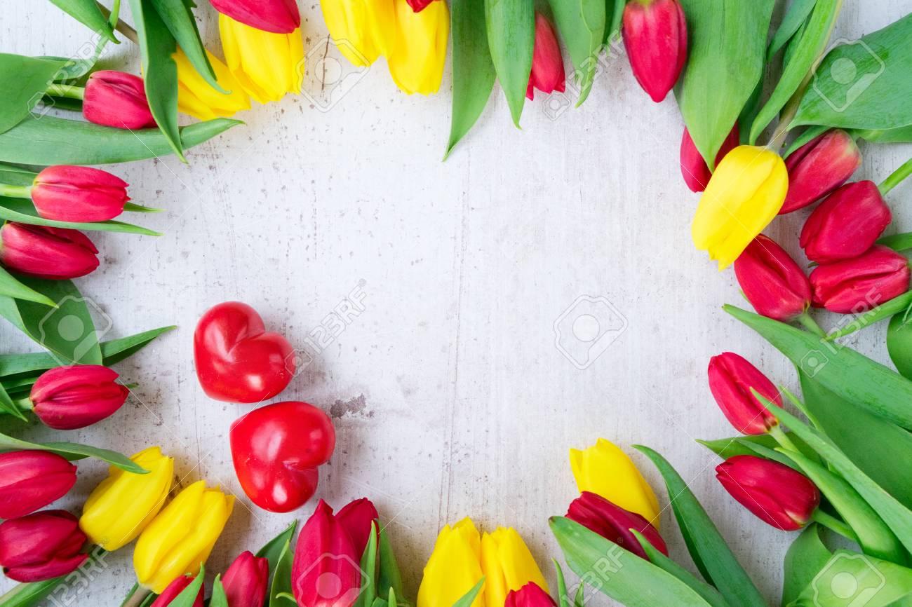 Flores Frescas De Tulipanes Amarillos Y Rojos Con Dos Corazones