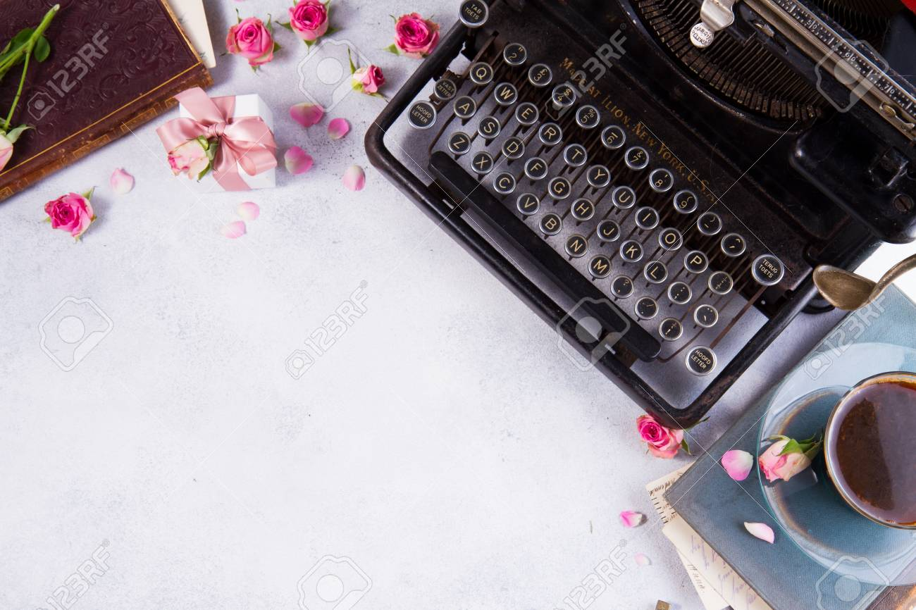 Workspace with vintage typewriter, cup of coffee and books - 75101012