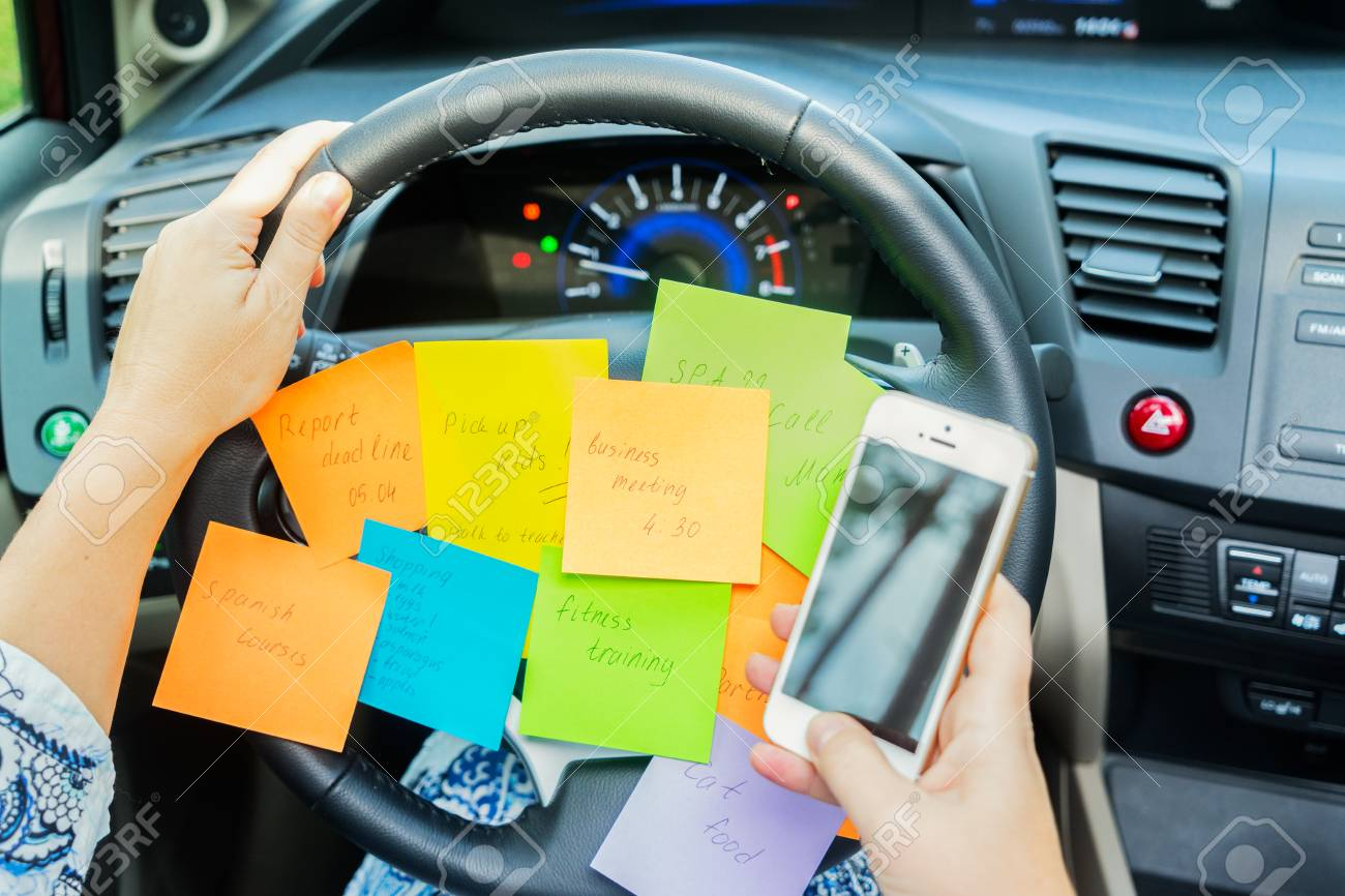 To do list in a car on driving wheel and hand holding phone - busy day concept - 76972011