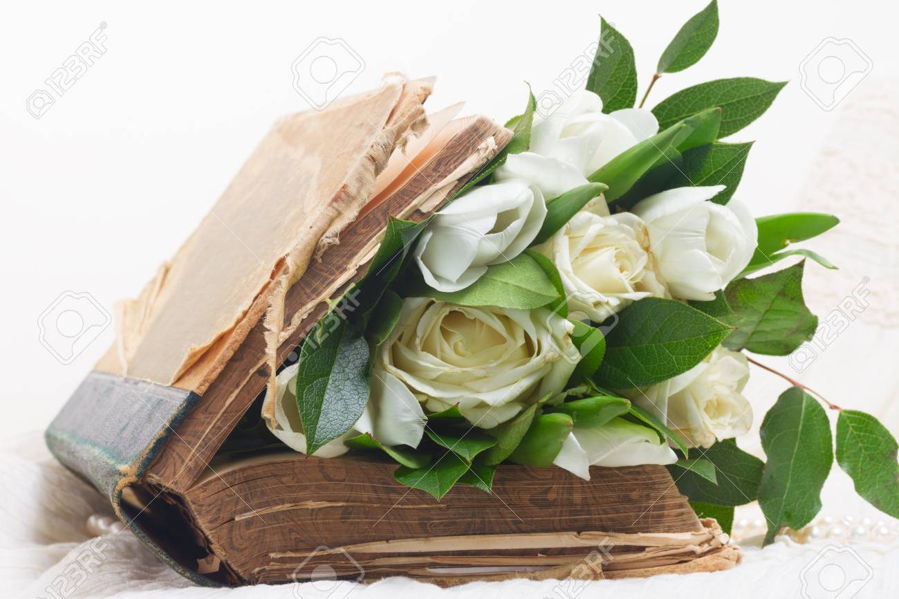 Old Book With White Fresh Flowers And Green Leaves On Romantic