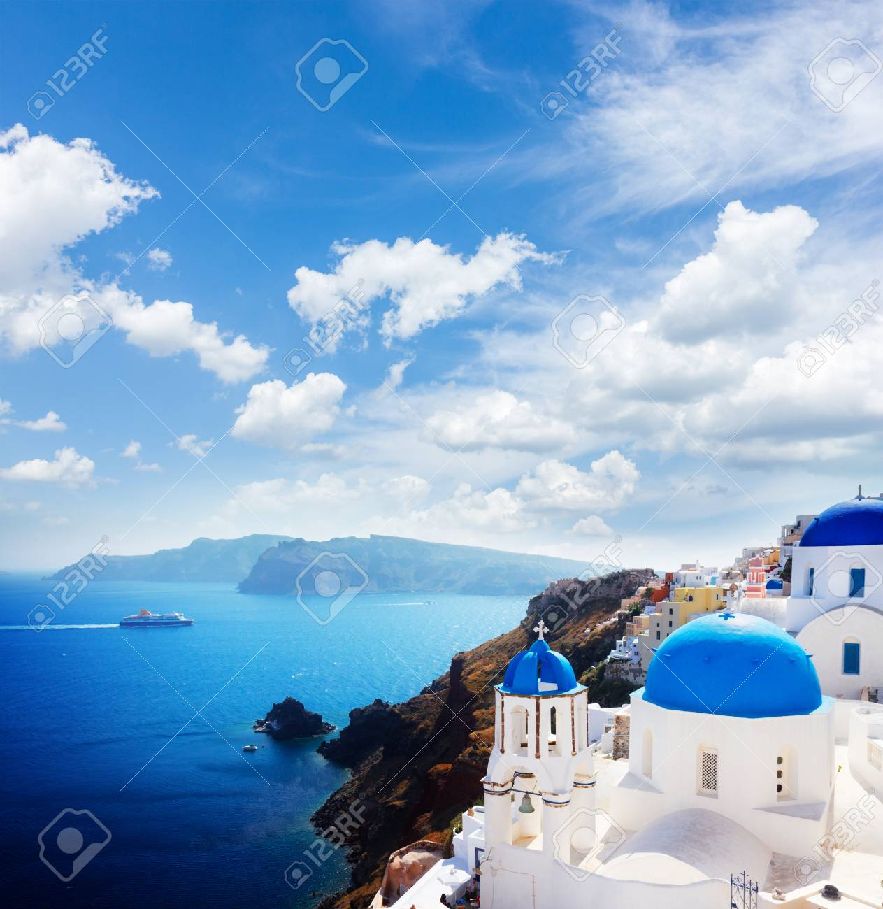volcano caldera with blue church domes at sunny day with cloudy sky, Oia, Santorini - 94776513