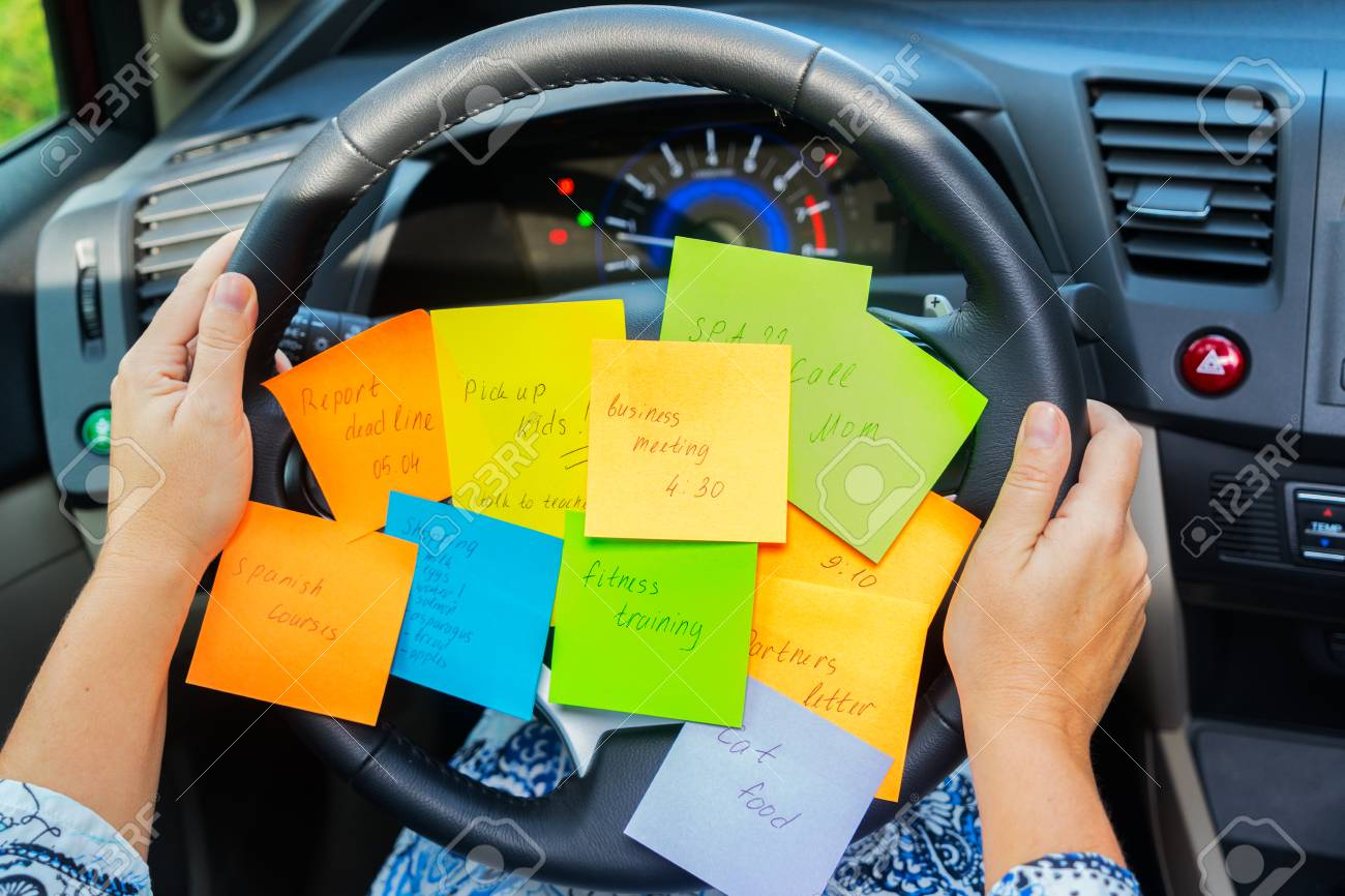 Two hands holding driving wheel and to do list in a car - busy day concept - 103215554